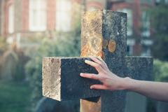 Hand touching a gravestone Stock Photos