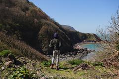 Woman walking across rocky terrain - stock photo