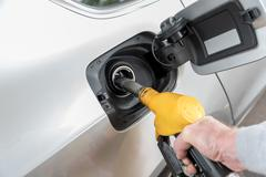 Hand holding fuel pump nozzle and refilling car - stock photo