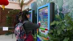 Two girls play video games on big touch display in public area Stock Footage