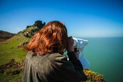 Woman looking through telescope by the sea - stock photo