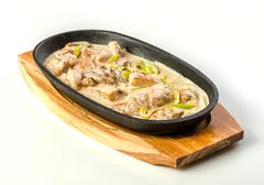 Chicken with cream in pan Stock Photos