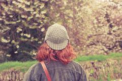 Woman in deerstalker hat looking at trees Stock Photos