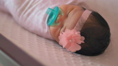 Close up of a newborn baby wrapped in a blanket laying in a crib Stock Footage