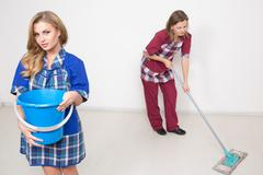 Stock Photo of two different cleaners compete. poor staff. wash the floor, clean office