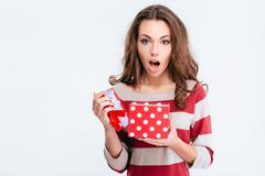 Amazed woman holding gift box - stock photo
