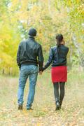 Affectionate couple taking walk in autumn park - stock photo
