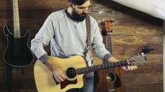 bearded man tuning an acoustic guitar slow motion - stock footage