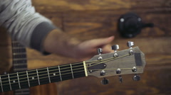 Close up mans hands tuning an acoustic guitar slow motion Stock Footage