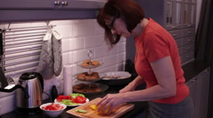 Woman cuts yellow pepper on a wooden cutting board - stock footage