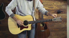 Stock Video Footage of close up mans hands tuning an acoustic guitar slow motion