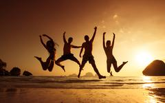 Group of friends jumps on sunset sea backdrop - stock photo