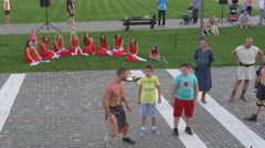 Men in medieval costume and two boys doing push ups in Alba Iulia Stock Footage