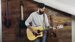 bearded man playing an acoustic guitar slow motion - stock footage
