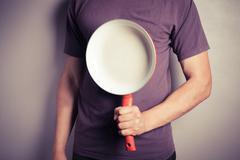 Man with frying pan Stock Photos