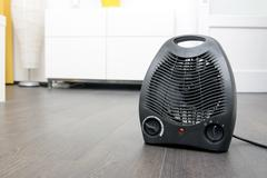Black electric heater on laminate floor in the room Stock Photos