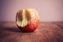 Half eaten apple on wooden table - stock photo