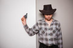 Young cowboy standing against dual colored background - stock photo