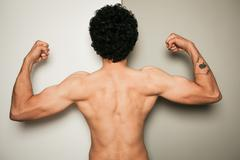 Rear view of shirtless man against dual colored background - stock photo