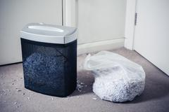 Paper shredder and bag of shredded documents - stock photo