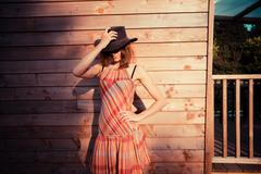Young woman wearing cowboy hat by a cabin - stock photo