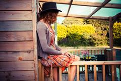 Woman wearing cowboy hat sitting on porch - stock photo