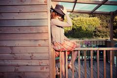 Woman wearing cowboy hat sitting on porch - stock photo
