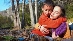 Autumn emotion love. Two brother and sister kissing sitting in park Stock Footage
