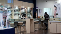 Female optician finding a suitable glasses to customer - stock footage