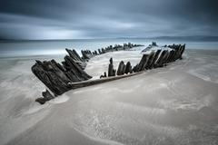 Ireland, Kerry, Rossbeigh Strand, Remnants of wooden rowboat in beach sand - stock photo