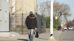 Man in Coat and Carrying Bag Walks by Mission Entrance Stock Footage