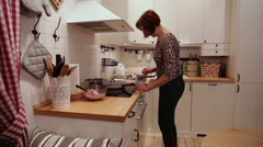 The woman in the kitchen includes a stove Stock Footage
