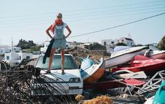 Woman standing on car in scrap yard Stock Photos