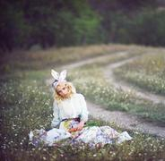 Young woman in dressed as bunny sitting in meadow - stock photo