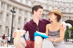young couple sitting together by admiralty arch - stock photo