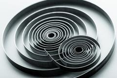 Abstract metallic spirals on grey background - stock photo