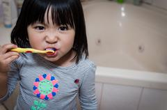 Australia, Melbourne, Young girl brushing teeth in bathroom - stock photo