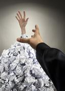 Helping hand saving buried businessman - stock photo