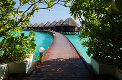 Maldives, View along elevated footbridge leading across water to row of stilt Stock Photos