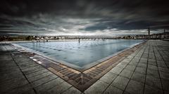 France, Bordeaux, Storm clouds over Miroir d'eau - stock photo