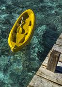 Indonesia, East Nusa Tenggara, Ende, Flores, Empty yellow canoe tied to wooden Stock Photos