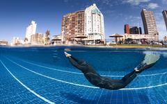 South Africa, KwaZulu Natal, Durban, Man wearing monofin diving in swimming pool - stock photo