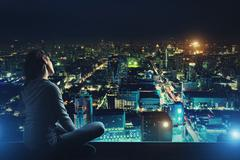 Pensive woman is looking at night city Stock Photos