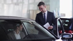 Salesman assuring buyer in selection of this car - stock footage