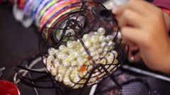 Hand of the girl stacks pearl beads into the wheel Stock Footage