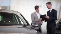 Sales manager assisting client in a car dealership - stock footage