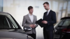 Vehicle dealer assisting client in a motor show Stock Footage