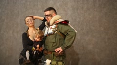 Family with a small child in costumes poses at Everycon Stock Footage