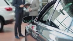 Car dealer and customer making a deal - stock footage