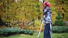 A girl dressed as a Sith Inquisitor with red light sward in the park Stock Footage